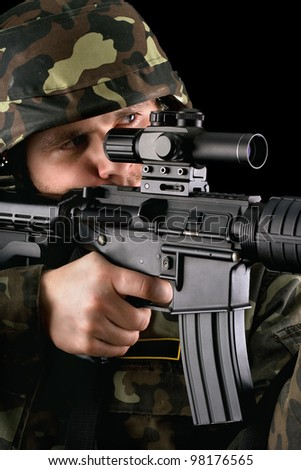 Armed soldier taking aim in studio. Closeup