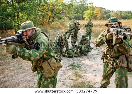 Armed soldiers evacuate the injured fellow  in forest - stock photo