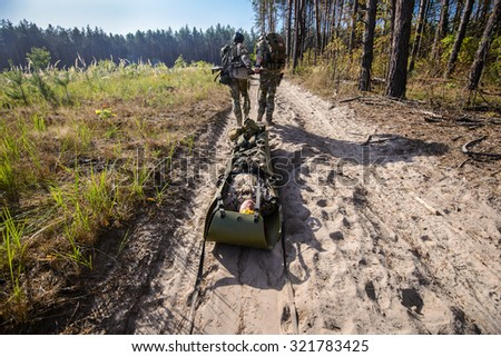 Armed soldiers evacuate the injured fellow on stretcher in forest - stock photo