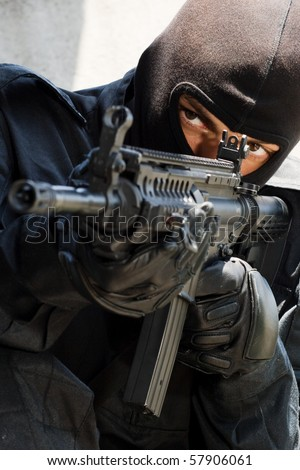 Armed terrorist in black mask and black uniform aiming with a gun. Trooper in black mask targeting with American M-4 rifle. Unknown armed forces in East Ukraine. Portrait of good or bad guy