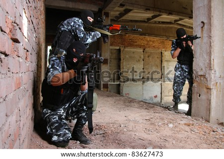 Armed terrorists in ruined building.Group of armed and dangerous soldier in uniform and black mask aiming with rifle.East Ukraine guerrilla separatists in ruins.Danger,big guns