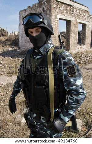 Armed-to-teeth soldier outdoors - stock photo