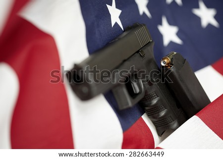 Armed United States of America gun and USA flag selective focus closeup - stock photo
