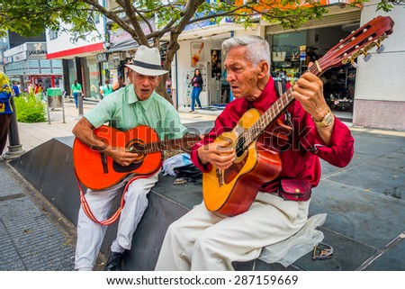 ARMENIA, COLOMBIA - FEBRUARY 23, 2015: two unidentify indigenous men playing guitar in the commercial street of Armenia - stock photo