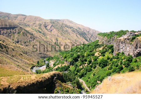 Armenian landscape with mountains, river, rocks and forest.