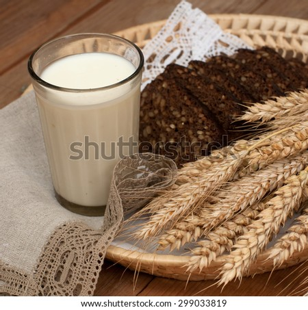 Armful of ears, fresh bread and a glass of milk on a straw tray with a linen napkin