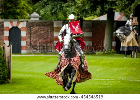 Armored knight suited for battle on horseback, charging in gallop. Galloping it the fastest gait of a horse, and because of the speed the warrior looks even more impressive - stock photo