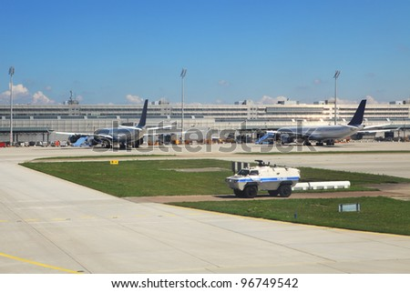 Armored police vehicle secures perimeter and exit to runway and two passenger airliners on the background standing at the gates in Munich International Airport, Germany. - stock photo