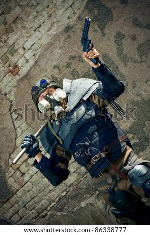 armored postnuclear fighter aiming his gun - stock photo