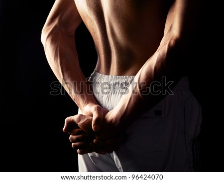 arms and back of a young muscular man, isolated against black studio background - stock photo