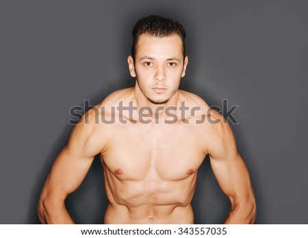 Arms and torso of muscular male bodybuilder flexing biceps - stock photo