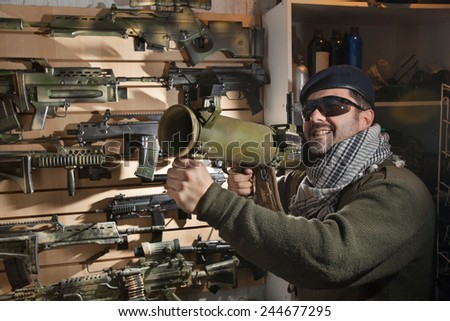 Arms merchant in the beret and sunglasses with the jet grenade launcher on the weapon display background
