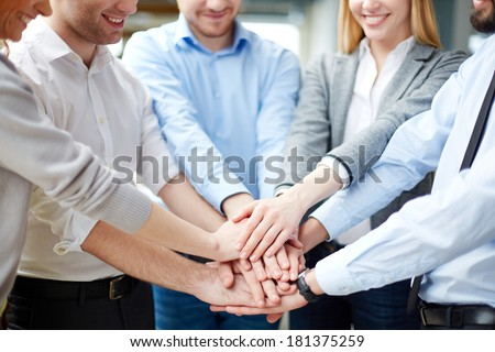 Arms of business partners keeping their hands on top of each other symbolizing teamwork - stock photo