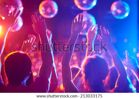 Arms of friends dancing in night club - stock photo