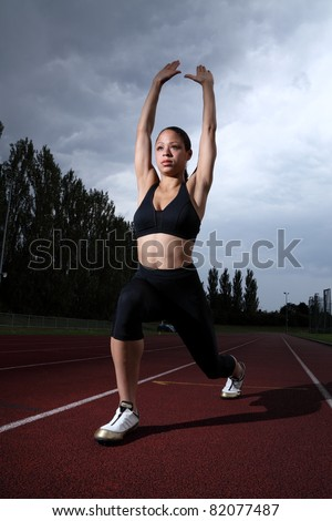 Arms raised doing lunge warm up stretch for fit young athlete woman on athletics running track wearing black lycra sports outfit and running spikes. Dark grey cloudy sky in background.