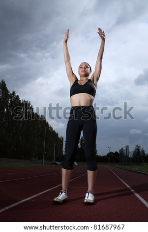 Arms raised in success for beautiful fit young female athlete standing on running track wearing black lycra sports outfit and running spikes. Grey cloudy sky in background.