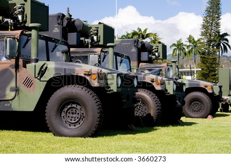 Army camouflage Humvees lined up in formation - stock photo