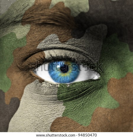 Army camouflage on human face - stock photo