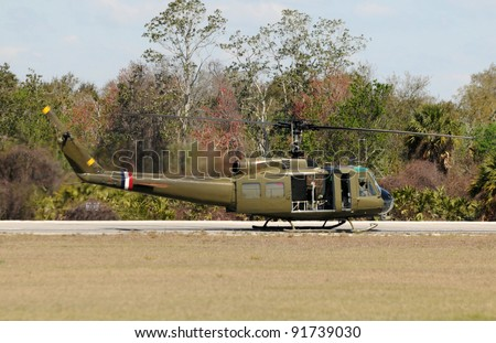 Army helicopter landing in a remote field - stock photo
