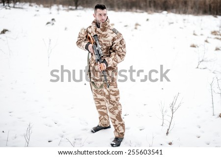 Army ranger with automatic machine gun performing patrol in a snowy forest - stock photo
