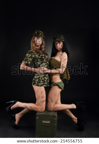 army sexy girls, two long legs soldier woman sitting on ammunition box wear military camouflage uniform cap full length over black background - stock photo