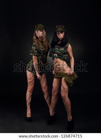 army sexy girls, two long legs soldier woman wear military camouflage uniform cap full length over black background