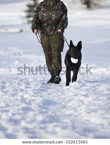 Army soldier is walking the dog outdoor in the snow.