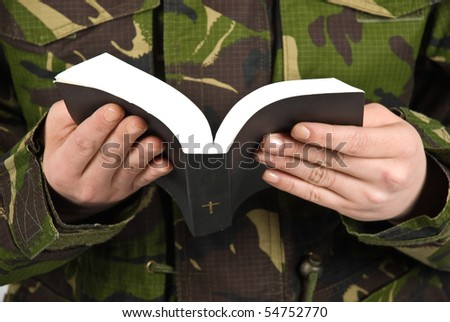 Army soldier reading bible ,selective focus on book and hands - stock photo