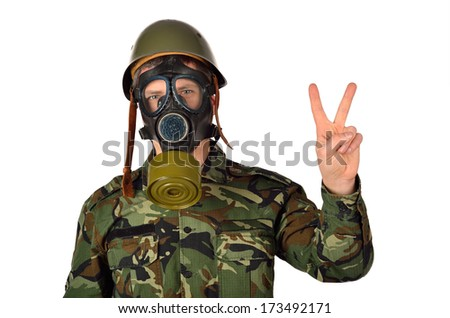 Army Soldier with Green Helmet And Gas Mask Peace gesture - stock photo