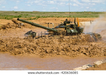 Army tank crosses the water obstacle at the landfill