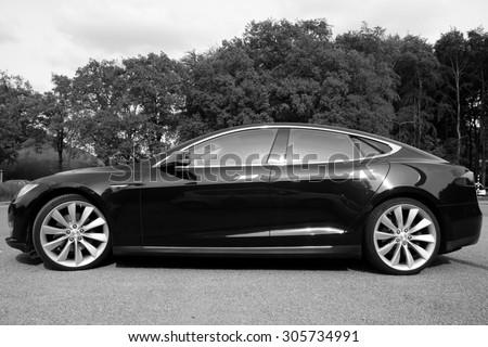 Arnhem, The Netherlands - May 17, 2015: : Black Electric Tesla Motors Model S parked on a parking lot (black white). Tesla Motors is an American automotive and energy storage company.  - stock photo