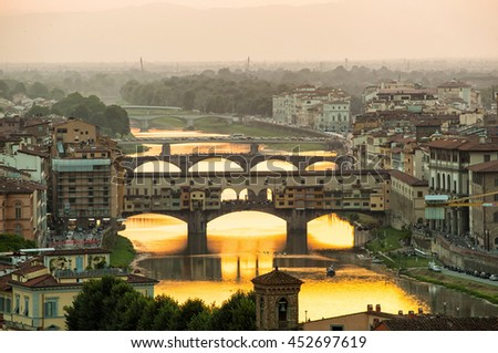 Arno river and famous Ponte Vecchio enlighten by the warm sunlight. Florence, Italy.