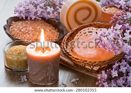 Aroma candle, sea salt, brown sugar, natural soap and lilac flower   - stock photo