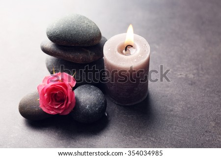 Aroma candle with pebbles and flower  on grey background - stock photo