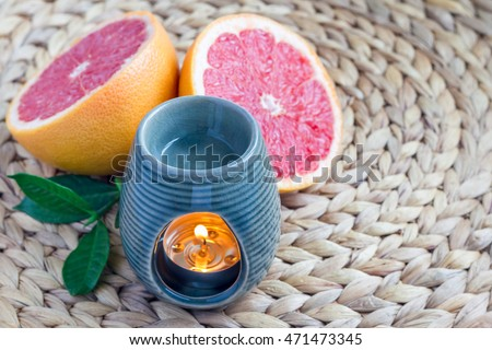 Aroma lamp with grapefruit essential oil on woven mat, grapefruits on background, horizontal