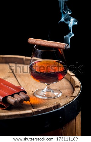 Aroma of Cuban cigars and cognac on black background - stock photo