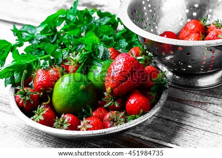 Aroma of summer fruits.Dish with ripe large strawberries,lime and peppermint leaves