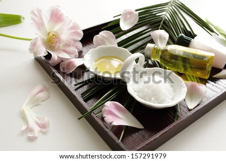 Aroma oil with salt and flowers on wooden tray - stock photo