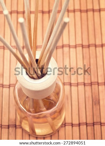 Aroma sticks in bottle on placemat, overhead view, selective focus - stock photo