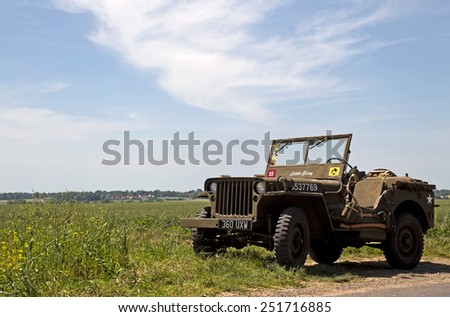 AROMANCHES, FRANCE - JUNE 6: A vintage WW2 Jeep is parked outside an allied soldiers war cemetery before attending the 70th D-Day anniversary celebrations on June 6, 2014 in Aromanches - stock photo