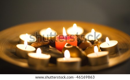 Aromatherapy arrangement with zen stones, scented lit candles and sticks on wooden plate. Shallow dof