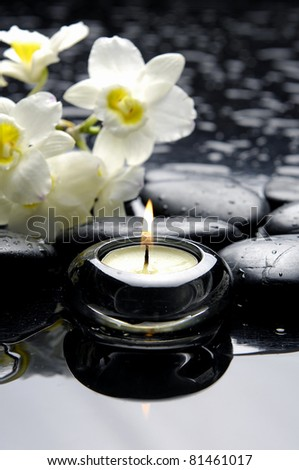 aromatherapy candle and zen stones with branch white orchid - stock photo