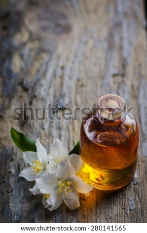 Aromatherapy concept. Massage oil and jasmin flower on rustic wooden table. - stock photo