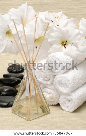 Aromatherapy diffuser, towel, rocks and flower in a spa - stock photo