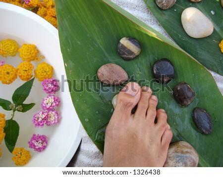 Aromatherapy foot massage treatment using warm pebbles. - stock photo