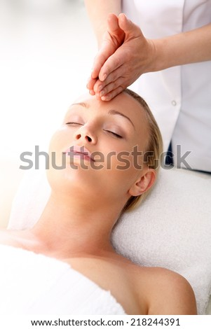 Aromatherapy, medicine east, natural medicine .Beautician beautiful woman massaging her temples . Woman in a beauty salon. Masseur massaging a woman in a spa. - stock photo