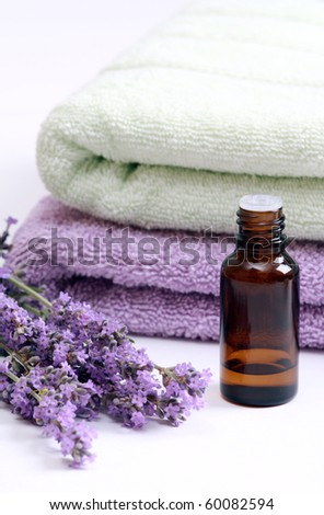 Aromatherapy oil and lavender flowers against terry towels - stock photo