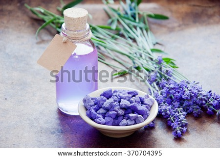 Aromatherapy oil and lavender, lavender spa, Wellness with lavender, lavender Scented stones lavender syrup on a wooden background - stock photo