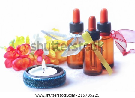 Aromatherapy oil bottles with fresh flowers  and candle - stock photo