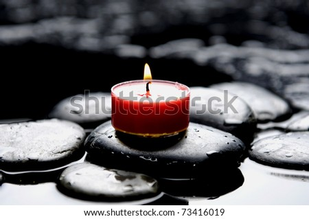 Aromatherapy red candle burning over stones in a spa - stock photo